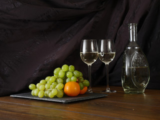 Still life: white wine and fruits.