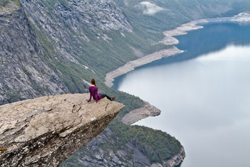 Girl sitting on Trolltunga rock (Troll's Tongue rock) and looking at Norwegian mountain landscape