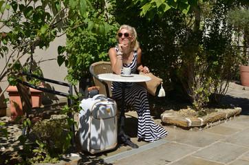 Woman in elegant dress sitting in Mediterranean yard with elegant suitcase