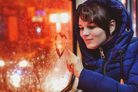 Young single woman in blue jacket sitting in an empty tram and paints on glass heart.