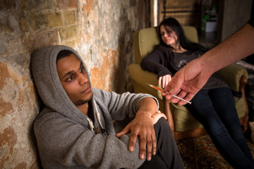 Drugs concept. Disease concept. Drug dealer's hand - image of Mafia offering young people to take drugs.
