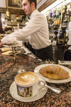 The typical Milanese breakfast with cappuccino and homemade brioche at the old Cafe Cova, icon of Milan, Lombardy