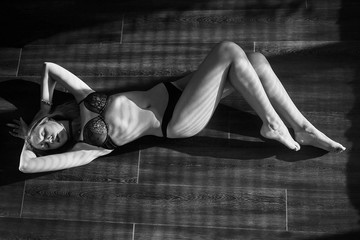 blond girl in lingerie lying on floor in sunlight, monochrome