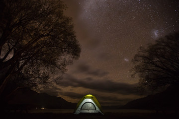 A tent glowing under in a night full of stars
