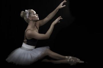 Beautiful ballerina in seated dance pose