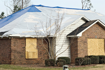 tornado damaged brick house with a tarp on the roof