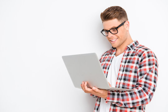 Smiling young man in glasses holding laptop and typing