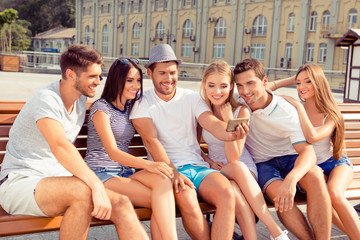 Six happy joyful friends sitting on bench and making photo on sm