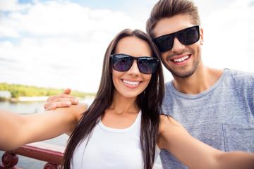 Selfie of happy cute lovers in glasses having walk in city