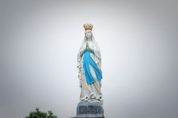 Soft focus. Statues of Holy Women on cloudy sky background / Statue of the Virgin Mary with soft tone background.