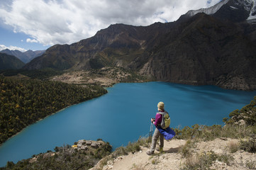 A trekker stands above the turquoise blue Phoksundo Lake in the Dolpa region, Himalayas, Nepal, Asia