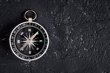 compass on dark background concept - direction motion top view