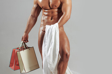 naked muscular man with shopping bags