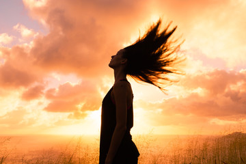 Feeling free. Happy woman outdoors with her hair blowing in the wind.