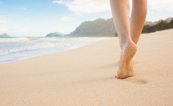 Woman walking on a beautiful white sand beach in  Hawaii.