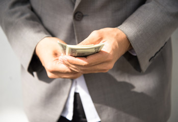 Business executive in formal suit giving money as a bribe, select focus