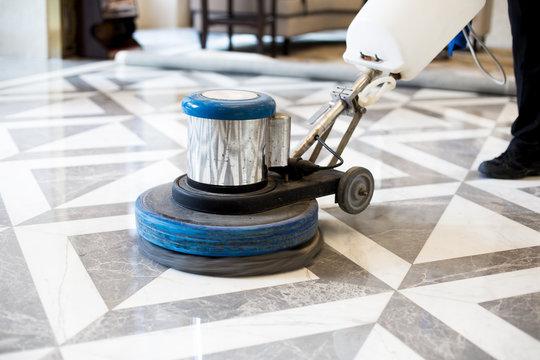 man polishing marble floor in modern office building
