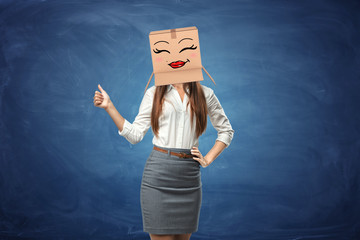Young beautiful woman showing her thumb up and wearing cardboard box with drawn smiley face