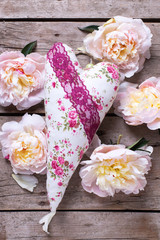 Decorative heart and  pink peonies flowers on aged wooden backgr