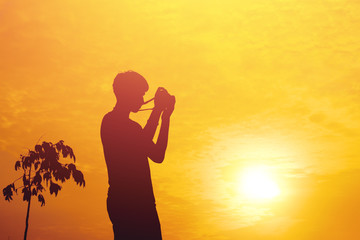 Silhouette of young photographer holding a camera on sunset.