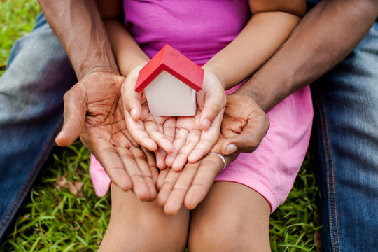 Hands of family together holding house in green park - family house concept