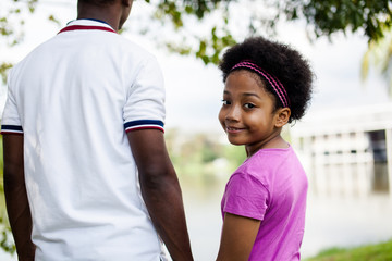 Father holding hands of daughter - African American family