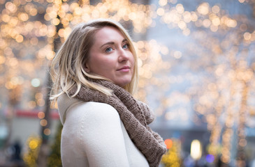 Winter portrait of young attractive woman with Christmas lights