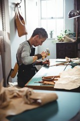 Craftswoman hammering leather