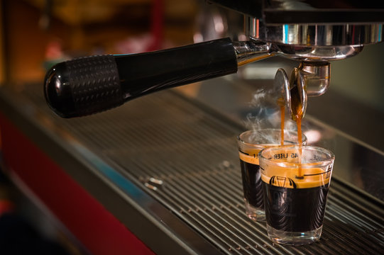 Close up image of espresso pouring into glass shot