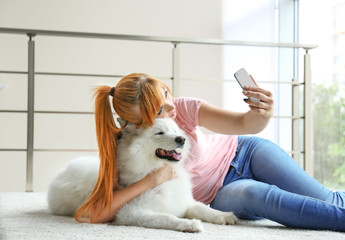 Girl taking selfie with Samoyed dog