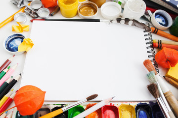 Colorful drawing supplies frame for blank sketchbook. Empty white notebook surrounded by paintbrushes and paints, mockup. Art, workshop, painting, inspiration, craft, creativity concept