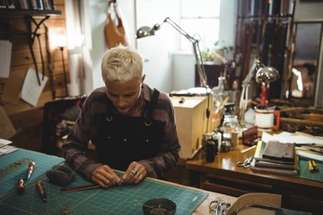 Attentive craftswoman cutting a piece of leather