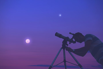 Man looking at the night sky with telescope beside him.
