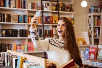 Smiling happy girl taking selfie while sitting in library