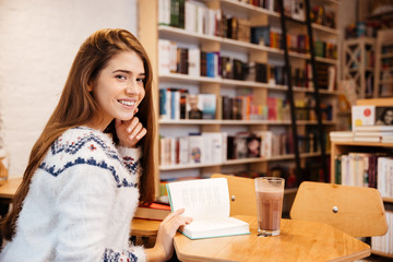 Girl sitting at the table and reading book in library