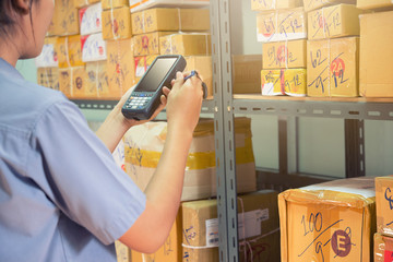 worker using tablet scanner checking the boxes on shelve in warehouse.