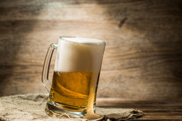 Beer poured into mug standing on wooden table