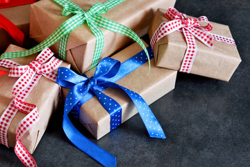 Happy New Year - Christmas gifts in boxes with ribbons on a black  background