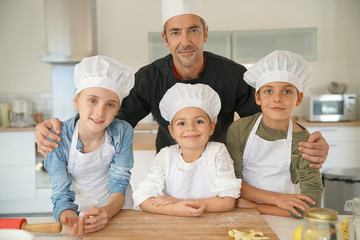 Portrait of happy pastry chef together with kids in cooking class
