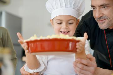 Portrait of cute little girl holding homemade apple pie