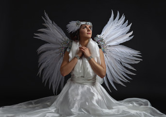 Young beautiful woman in angel costume with wings, natural feath