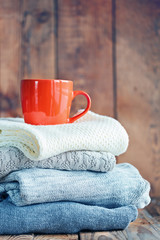 Sweaters Closeup, Stack of knitted winter clothes with red cup on wooden background. Toning image