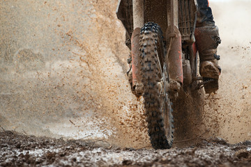Motocross driver splashing mud on wet and muddy terrain Wall mural