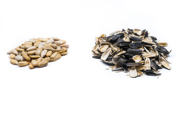 Closeup of piles of peeled sunflower seeds and their husks isolated on white background