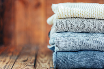 Stack of knitted winter clothes on wooden background, sweaters, space for text. Toned image.