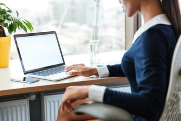 Cropped image of business woman using laptop