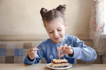 Cute little girl eating tasty cake in kitchen