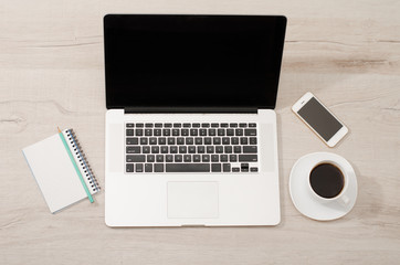 Top view of a laptop, smart phone, a notebook with a pencil and a cup of coffee