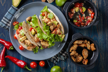 Authentic mexican tacos with chicken and salsa with avocado, tom