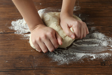 Woman kneading dough on wooden kitchen table, close up